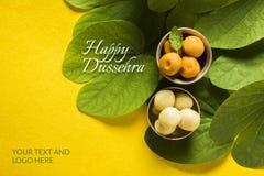印地安节日dussehra,显示有传统印地安甜点pedha的金黄叶子在黄色背景的银色碗,招呼c 免版税图库摄影