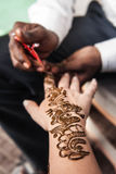 印地安街道大师使用无刺指甲花浆糊或mehndi应用 免版税图库摄影