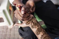 印地安街道大师使用无刺指甲花浆糊或mehndi 免版税库存照片