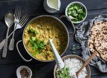 印地安dhal在烹调平底锅用茉莉花米、香菜和整个五谷小面包干在黑暗的背景,顶视图 平的位置 免版税库存照片