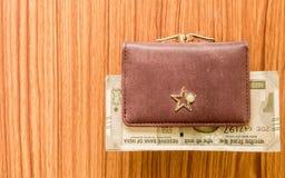 印度五百500卢比在棕色颜色钱包皮革钱包的钞票在一张木桌上 企业财务经济概念 免版税库存照片