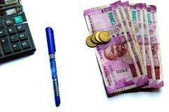印度卢比和硬币堆、计算器和笔 免版税库存图片