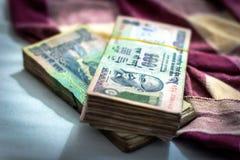 印度卢比货币,与模糊的印地安毯子的金钱在背景 库存照片