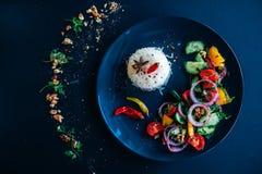 印度大米,沙拉,辣椒 黑暗的背景,黑色的盘子,顶视图 库存图片