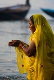 印度妇女杯祈祷的平原河瓦腊纳西 免版税图库摄影