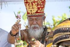 印度尼西亚人民庆祝巴厘语新年和春天到来  老婆罗门举办在海滩Ketewe的宗教仪式 免版税库存照片