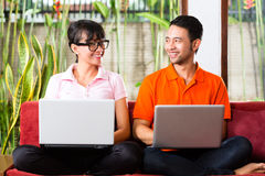 在长沙发的亚洲夫妇有膝上型计算机的 库存图片