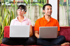 在长沙发的亚洲夫妇有膝上型计算机的 免版税库存图片