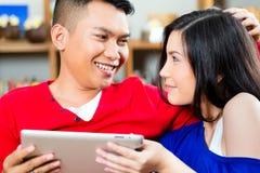 在长沙发的亚洲夫妇有片剂个人计算机的 免版税库存图片