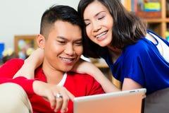 在长沙发的亚洲夫妇有片剂个人计算机的 免版税图库摄影