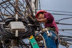 印度尼西亚电工修理工作者将修理网络缆绳和导线线在电杆 印度尼西亚雅加达 jule 图库摄影