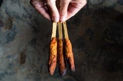 印度尼西亚盘龙目岛:在手中心满意足Pusut在棍子举行的用卤汁泡的肉混合在地面 图库摄影