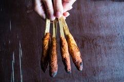 印度尼西亚盘龙目岛:在手中心满意足Pusut在棍子举行的用卤汁泡的肉混合在桌 图库摄影