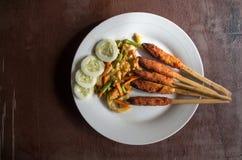 印度尼西亚盘龙目岛:心满意足Pusut在棍子留出的拷贝空间的用卤汁泡的肉混合 库存图片