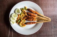 印度尼西亚盘龙目岛:心满意足Pusut在棍子的用卤汁泡的肉混合 库存图片