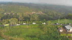 印度尼西亚领域、小山和村庄空中风景有一条路和汽车的在巴厘岛海岛上  影视素材