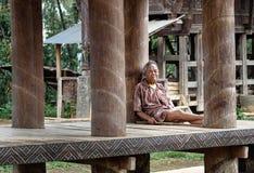 印度尼西亚年长人在塔娜Toraja坐在tongkonan传统房子下地板  库存图片