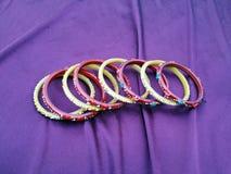 印度手镯 在紫罗兰色背景的许多颜色手镯 免版税库存照片