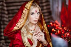 印度红莎丽服的美丽和肉欲的白肤金发的女孩和ho 图库摄影