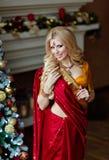印度红莎丽服的美丽和肉欲的白肤金发的女孩在附近 免版税库存照片