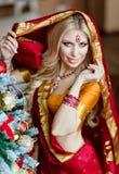 印度红莎丽服的美丽和肉欲的白肤金发的女孩在附近 免版税库存图片