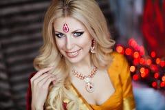 印度红莎丽服的美丽和肉欲的白肤金发的女孩在bac 库存图片