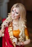 印度红莎丽服的美丽的白肤金发的女孩在圣诞节t附近 库存照片