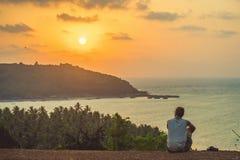 印度,果阿- 2017年3月15日:一个人坐在小山顶部并且看太阳集合在海 库存图片