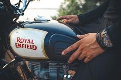 印度,果阿- 2017年4月6日:供以人员有一块手表的` s手在皇家埃菲尔德摩托车的汽油箱 库存照片