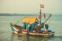 印度,果阿- 2017年2月2日:有印地安人旗子的一个渔船航行入海 图库摄影