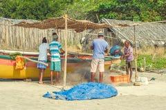 印度,果阿- 2016年11月19日:渔夫在一条黄色小船附近的织法网 免版税图库摄影