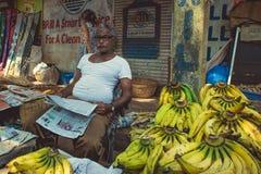 印度,果阿- 2017年2月9日:香蕉卖主读一张报纸 库存图片