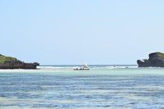 印度洋图象在两个岩石之间的单桅三角帆船航行 库存图片