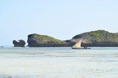 印度洋图象通过岩石的单桅三角帆船航行 免版税图库摄影