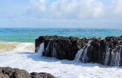 印度洋挥动倾销反对黑暗的玄武岩岩石在海洋海滩Bunbury西澳州 免版税库存图片