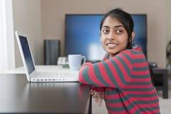 印第安女孩与膝上型计算机一起使用 库存图片
