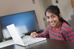印第安女孩与膝上型计算机一起使用 免版税库存照片
