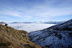 印象深刻的积雪覆盖的山有云彩昆斯敦NZ海的壮观的看法  库存照片