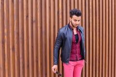 印象深刻的阿拉伯年轻人审查并且改正玻璃夹克 库存照片