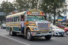 危地马拉- 2017年11月11日:有交通的危地马拉城街 公共交通工具每日看法,象五颜六色的鸡公共汽车,出租汽车 图库摄影
