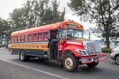 危地马拉- 2017年11月11日:有交通的危地马拉城街 公共交通工具每日看法,象五颜六色的鸡公共汽车,出租汽车 库存图片