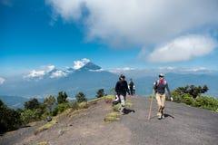 危地马拉- 2017年11月10日:waling在帕卡亚火山火山观点顶部的人们 圣佩德罗火山火山在背景中 库存照片