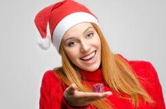危机圣诞节 拿着一个小圣诞节礼物的美丽的红色头发妇女 免版税库存照片