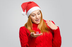 危机圣诞节 拿着一个小圣诞节礼物的美丽的红色头发妇女 库存照片