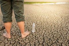 水危机,破裂的地球上的人在干燥水附近 免版税库存照片