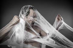 危险。在巨大的白色蜘蛛网缠结的人 库存图片