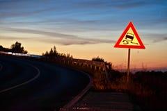 滑危险交通标志的弯曲的路 免版税库存图片