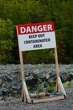 危险保持在岩石地面的污染的区域标志外面 库存图片