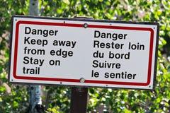 危险保持远离在足迹标志的边缘逗留 库存照片