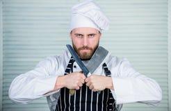 危险厨房 厨师准备好烹调 围裙和帽子举行刀子的确信的人 有胡子的人爱食物 免版税库存照片